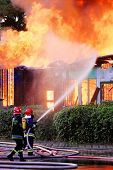 stock photo of firemen  - Firemen in action on burning ruins of building - JPG