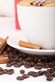 stock photo of scum  - Cappuccino cup with drawing on scum and coffee beans - JPG