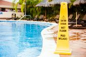 stock photo of skid  - Wet floor warning sign on a swimming pool in Mexico - JPG