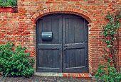 picture of wooden door  - Old wooden door and red brick wall of rural house in Italy - JPG