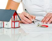 picture of home addition  - a woman signs a contract to purchase a home with a real estate agent - JPG