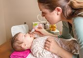image of nasal catarrh  - Mother cleaning mucus catarrh of adorable baby with a nasal aspirator - JPG