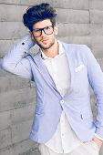 picture of blazer  - Portrait of cheerful trendy guy with black eyeglasses on wearing blue blazer jacket - JPG