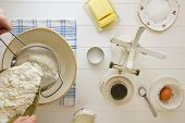 picture of devonshire  - Ingredients for English scones laid out on white wood with flour being sifted - JPG