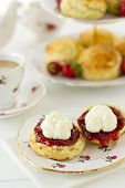 stock photo of devonshire  - English Cream tea scene with scones Cornish style on china plate with teacup and saucer - JPG
