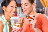 foto of ice cream parlor  - Young female customers or friends in an ice cream parlor with ice cream cornet - JPG