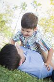 image of tickle  - Mixed Race Father and Son Playing Together in the Park - JPG