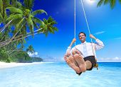 stock photo of swings  - Businessman swinging at tropical beach - JPG