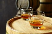 picture of tumbler  - Glasses of brandy in cellar with old barrels  - JPG