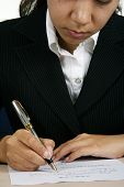 stock photo of person writing  - An asian businesswoman writing a document - JPG