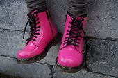 stock photo of skinheads  - Nice pink punk alternative girl or woman Military skinhead shoes - sitting tough