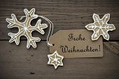 stock photo of weihnachten  - Ginger Bread Stars with white Decoration and a Label with the German Words Frohe Weihnachten which means Merry Christmas - JPG