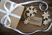 picture of ginger bread  - Tag with the French Word Merci which means Thanks on a Tag with Christmas Decoration like a brown Gift and decorated Ginger Bread Cookies - JPG