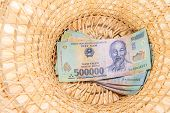 stock photo of dong  - Vietnamese money dong backnote inside asian style hat - JPG