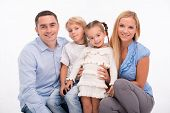 image of squat  - Happy family of father mother son and daughter smiling  squatting looking  at camera  isolated on white background - JPG