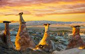 image of fairy-mushroom  - Rocks looking like mushrooms dramatically lit by a sunset in Cappadocia - JPG