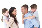 stock photo of piggyback ride  - Side view of happy parents giving piggyback ride to children over white background - JPG