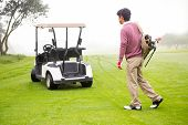 image of buggy  - Golfing walking toward the buggy at the golf course - JPG