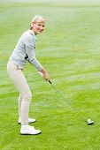 stock photo of ladies golf  - Lady golfer on the putting green on a foggy day at the golf course - JPG