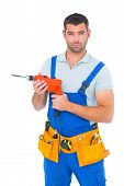 pic of overalls  - Portrait of confident male carpenter in overall holding drill machine on white background - JPG