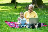 stock photo of grandparent child  - grandfather and child using tablet computer in park - JPG
