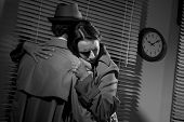 stock photo of office romance  - Detective consoling and hugging a young woman in his office film noir scene - JPG