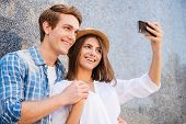 foto of love making  - Beautiful young loving couple making selfie with smart phone and smiling while leaning at the wall