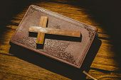 stock photo of crucifix  - Crucifix icon on the bible on wooden table - JPG