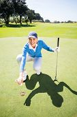 foto of ladies golf  - Smiling lady golfer kneeling on the putting green on a sunny day at the golf course - JPG