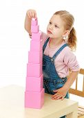 picture of montessori school  - Little girl collects the pink pyramid - JPG