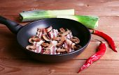 pic of bacon strips  - Strips of bacon with mushrooms in pan - JPG