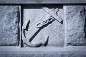stock photo of navy anchor  - A Navy ship anchor carved into granite stone - JPG