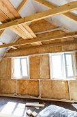 picture of glass-wool  - Inside wall heat isolation with mineral wool in wooden house building under construction - JPG