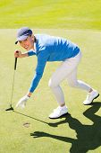 picture of pick up  - Female golfer picking up golf ball on a sunny day at the golf course - JPG