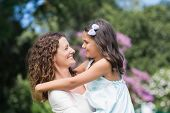 stock photo of daughter  - Happy mother and daughter smiling at each other in the garden - JPG