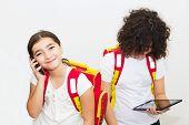 foto of ten years old  - Two ten year old schoolgirls using computer tablet and smart phone - JPG