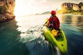 image of kayak  - Young lady paddling the kayak in a bay with limestone mountains - JPG