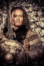 stock photo of sword  - Ancient male warrior in armor holding sword and shield - JPG