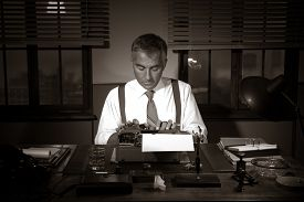 stock photo of 1950s style  - Professional handsome reporter working at office desk 1950s style.