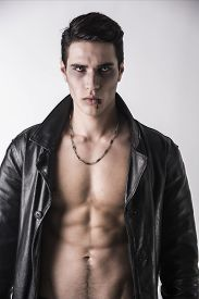 foto of jacket  - Portrait of a Young Vampire Man in an Open Black Leather Jacket Showing his Chest and Abs Looking at the Camera on a White Background - JPG
