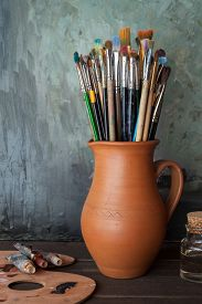 picture of paint pot  - Paintbrushes in a jug from potters clay palette paint tubes and bottle of oil in artist studio - JPG