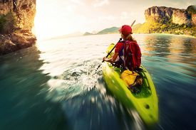 picture of kayak  - Young lady paddling the kayak in a bay with limestone mountains - JPG