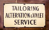 stock photo of tailoring  - A Vintage Sign For A Tailor And Valet In London England