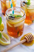 stock photo of mason  - Homemade honey iced tea in mason jars with straws - JPG