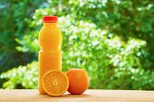 image of orange  - Bottle of orange juice and the orange and the half of orange on the wooden table on the green blurred background - JPG