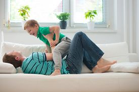 pic of titillation  - Little boy having fun with father on sofa at home - JPG