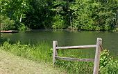 stock photo of split rail fence  - A section of split rail fence beside A peaceful lake - JPG