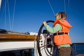 pic of sail-boats  - Little girl sailing with her life jacket on - JPG