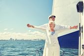 sailing, age, tourism, travel and people concept - happy senior couple enjoying freedom on sail boat poster