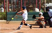 picture of fastpitch  - Fastpitch softball about to be hit by batter with catcher and umpire in positions. All logos have been removed.
